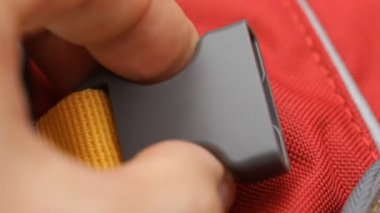 Plastic fastener on a red backpack — Stockvideo