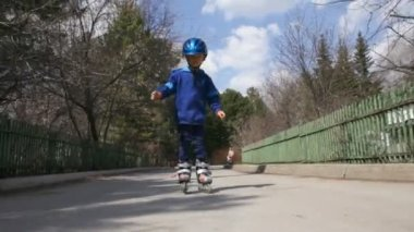 Little boy rides on roller skates — Stock video