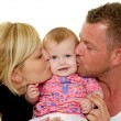 Mother and father are kissing baby - Stock Photo
