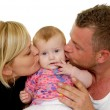 Stock Photo: Mother and father are kissing baby