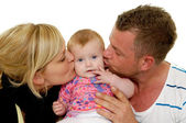Mother and father are kissing baby — Stock Photo