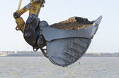 Excavator dredging a harbor — Stock Photo