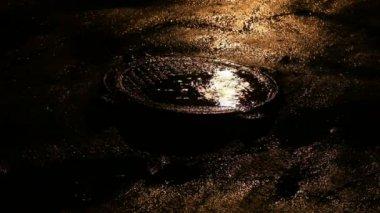 Night rain reflect on street manhole — Stock Video