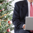 Businessman with pc by christmas tree — Stock Photo #2511549