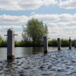 Poles in river — Stock Photo