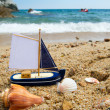 Toy saill boat at the beach - Stock Photo