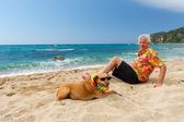 Man laying with dog at the beach — Stock Photo