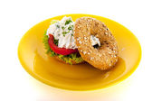 Bagel with cream cheese and herbs on plate — Stock Photo