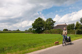 Elderly man at the bike with dog — Stock Photo