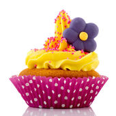 Pink cupcake with yellow cream and flower — Stock Photo