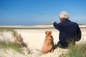 Homem com o cão na duna de areia — Fotografia Stock