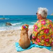 Senior man with dog on beach — Stock Photo