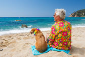 Alter Mann mit Hund am Strand — Stockfoto
