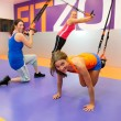 图库照片: Young woman doing suspension training