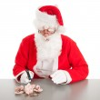 Santa breaking poor piggy bank — Stock Photo
