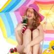 Sunbathing at the beach with colorful parasol — Stock Photo