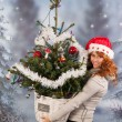 Winter woman with hat of Christmas Santa and tree — Stockfoto