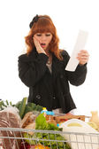 Woman with Shopping cart full dairy grocery scaring by receipt — Stock Photo