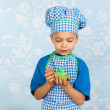 Stock Photo: Little boy in apron baking cupcakes