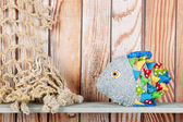 Stuffed funny fish on wooden background — Stock Photo