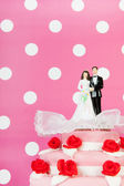 Wedding cake with couple on pink background — Stock Photo