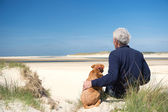Man with dog on sand dune — Stock Photo