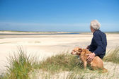 Man with dog on sand dune — Stock Photo