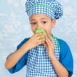 Little boy in apron baking cupcakes — Stock Photo