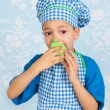 Little boy in apron baking cupcakes — Stock Photo #44156411