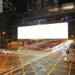 Big Empty Billboard at night in city with busy traffic — Stock Photo #17004381