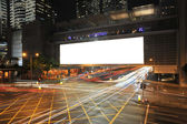 Big Empty Billboard at night in city with busy traffic — Stock Photo