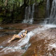 Sexy girl with bikini lying down in waterfall river — Stock Photo