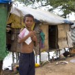 Boy in slum holding book want to go school - Stok fotoğraf