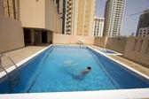 Man swim in swimming pool at roof of apartment, bahrain — Stock Photo