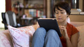 Girl touching tablet computer screen at home — Stock Photo