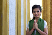 Asiatisk tjej hälsar i templet traditionellt sätt med båda händerna — Stockfoto