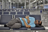 Sleeping in airport with eye cover — Stock Photo