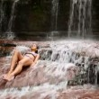 Stock Video: Sexy girl with bikini lying down in waterfall river