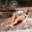 Sexy girl with bikini lying down in waterfall river - Stock Photo