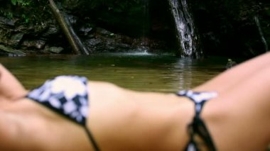 Sexy girl with bikini lying down in waterfall river — Stock Video