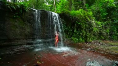 Sexy girl with bikini taking a shower in waterfall — Stock Video