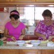 Stock Video: Mother daughter preparing meal together in kitchen