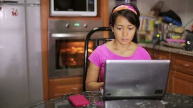 Woman sitting with laptop by oven in kitchen — Vidéo