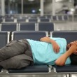 Sleeping in airport with eye cover - Stock Photo