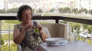 Old retired woman eating grapes on balcony — Stock Video