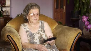 Old retired woman watching television — Stock Video