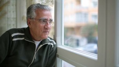 Senior man looking through window — Stock Video