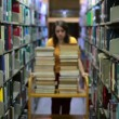 Distressed female student wandering between shelves — Stock Video #22358455