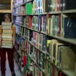 Distressed female student wandering between shelves — Stock Video #22358541