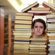 Sad female student gazing through house-shaped stack of books — Stock Video #22358919